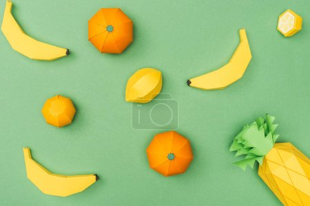 Foto de Vista superior de plátanos de papel hechos a mano, limones y mandarinas aisladas en verde - Imagen libre de derechos