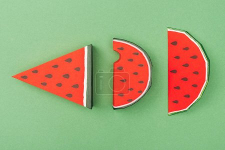 Photo for Top view of handmade paper watermelon slices isolated on green - Royalty Free Image