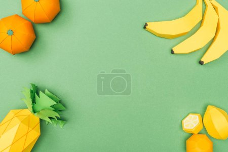 Photo for Top view of handmade paper bananas, lemons, tangerines and pineapple isolated on green - Royalty Free Image