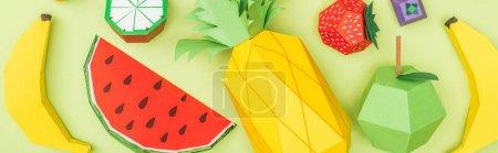 Foto de Panoramic shot of multicolored handmade paper fruits isolated on green - Imagen libre de derechos