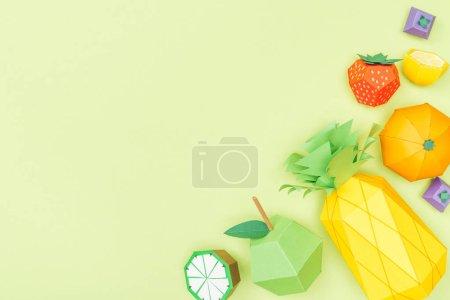 Foto de Top view of handmade colorful origami fruits isolated on green with copy space - Imagen libre de derechos
