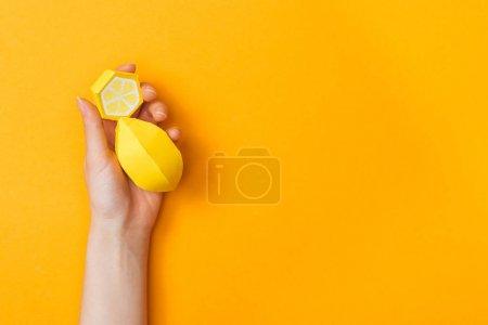 Photo pour Vue partielle de la jeune femme tenant des citrons en papier isolés sur orange avec espace de copie - image libre de droit