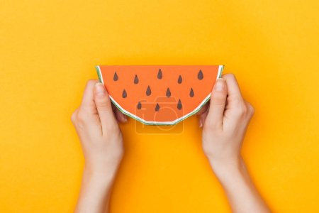 Photo for Cropped view of young woman holding paper watermelon on orange - Royalty Free Image