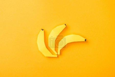 Foto de Top view of yellow paper bananas on orange - Imagen libre de derechos