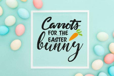 Photo pour Vue supérieure des carottes pour le lettrage de lapin de Pâques dans le cadre carré blanc près des oeufs peints de poulet sur le fond bleu - image libre de droit