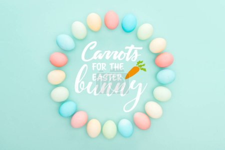 Foto de Top view of round frame made of painted chicken eggs on blue background with white carrots for the Easter bunny lettering - Imagen libre de derechos