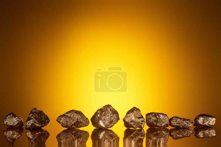 Photo pour Pierres brillantes d'or avec le reflet et la lumière arrière jaune - image libre de droit