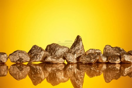 Photo pour Pile de pierres brillantes d'or dans la ligne avec la réflexion sur le fond jaune avec l'espace de copie - image libre de droit