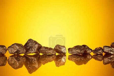 Photo pour Pierres brillantes d'or dans la ligne avec la réflexion sur le fond jaune avec l'espace de copie - image libre de droit