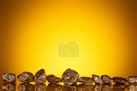 Photo pour Pierres brillantes d'or avec la réflexion sur le fond illuminé jaune - image libre de droit
