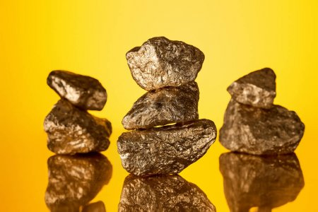Photo for Selective focus of three stacks of gold shiny stones with reflection isolated on yellow - Royalty Free Image