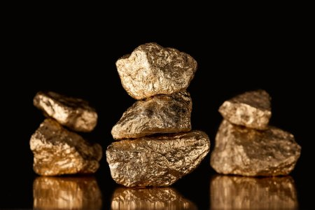 Photo for Selective focus of three stacks of gold shiny stones with reflection isolated on black - Royalty Free Image