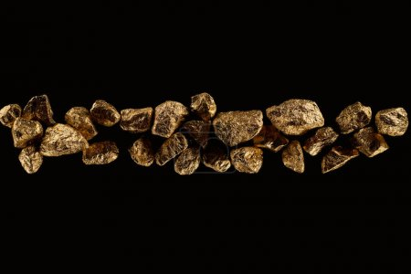Photo for Top view of golden textured stones arranged in row isolated on black - Royalty Free Image