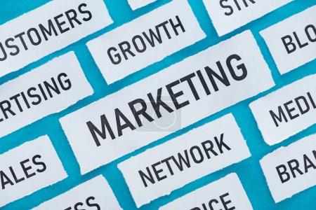 Photo pour Vue du haut des composants du marketing sur des morceaux de papier isolés sur le bleu - image libre de droit