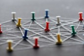 """Постер, картина, фотообои """"selective focus of colorful push pins connected with strings on grey, network concept"""""""