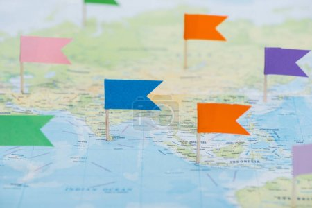 Photo pour Vue rapprochée des épingles à drapeau colorées sur la carte du monde - image libre de droit