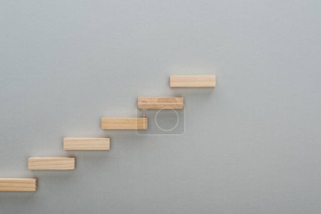 Photo for Top view of wooden blocks symbolizing career ladder isolated on grey with copy space - Royalty Free Image