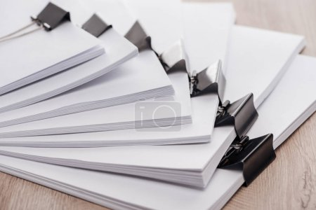 Photo for Arranged stacks of blank paper with metal binder clips on wooden desk - Royalty Free Image