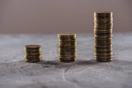 pièces d'or disposées en rangées sur une table isolée sur brun