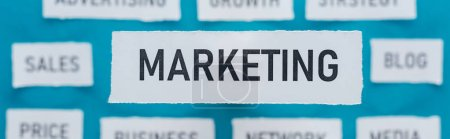 Photo for Panoramic shot of marketing word on pieces of paper on blue - Royalty Free Image