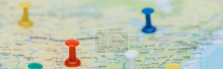 panoramic shot of colorful push pins on world map