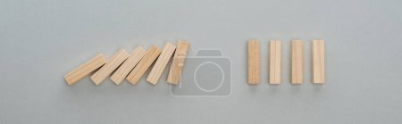 Photo for Panoramic shot of of falling wooden blocks isolated on grey, domino effect concept - Royalty Free Image