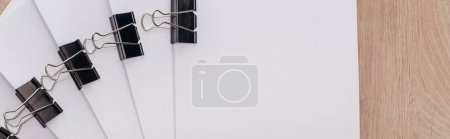 Photo for Panoramic shot of stacks of blank paper with metal paper clips and copy space - Royalty Free Image
