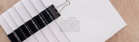Photo for Panoramic shot of stacks of blank paper with metal binder clips and copy space - Royalty Free Image