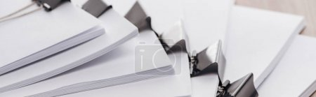 Photo for Panoramic shot of stacks of blank paper with metal binder clips - Royalty Free Image
