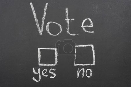 Photo for Top view of white vote, yes and no lettering on black chalkboard - Royalty Free Image