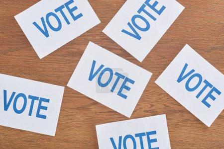 Photo pour Vue supérieure des cartes blanches avec le lettrage bleu de vote dispersé sur la table en bois - image libre de droit
