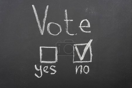Photo for Top view of white vote lettering and check mark near no word on black chalkboard - Royalty Free Image