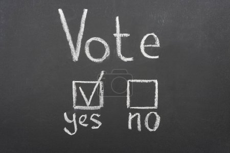 Photo for Top view of white vote lettering and check mark near yes word on black chalkboard - Royalty Free Image