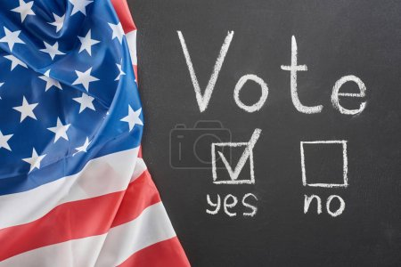 Photo for Top view of white vote lettering and check mark near yes word on black chalkboard near american flag - Royalty Free Image