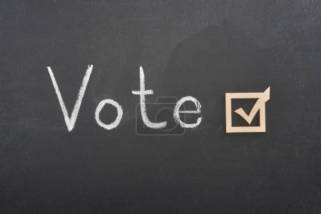 top view of white vote lettering near check mark on black chalkboard