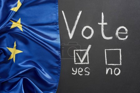 Photo for Top view of vote lettering and check mark near yes word on black chalkboard near European flag - Royalty Free Image