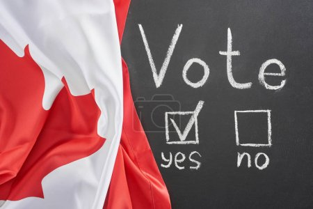 top view of vote lettering and check mark near yes word on black chalkboard near flag of Canada