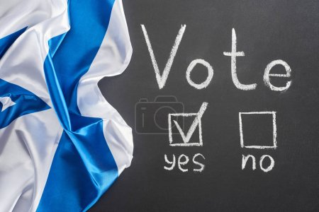 Photo for Top view of vote lettering and check mark near yes word on black chalkboard near crumpled flag of Israel - Royalty Free Image