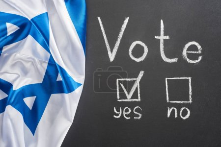 Photo for Top view of vote lettering and check mark in square near yes word on black chalkboard near flag of Israel - Royalty Free Image