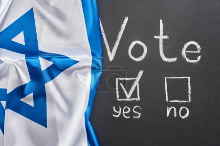top view of vote word and check mark near yes word on black chalkboard near flag of Israel