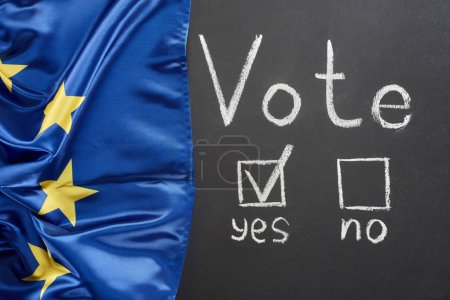 Photo for Top view of vote lettering and check mark near yes word on black chalkboard near flag of Europe - Royalty Free Image