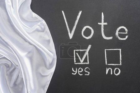 Photo pour Vue du haut du lettrage de vote et de la marque de contrôle près de mot oui sur le tableau noir près du drapeau blanc - image libre de droit