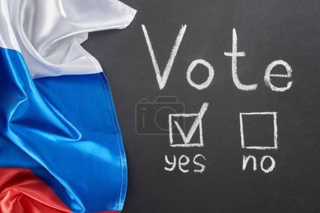 Photo pour Vue supérieure du lettrage de vote et de la marque de contrôle près de mot oui sur le tableau noir près du drapeau de la Russie - image libre de droit