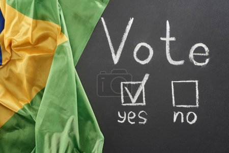 top view of vote lettering and check mark near yes word on black chalkboard near flag of Brazil