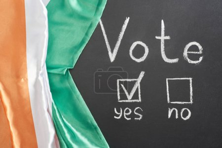 Photo for Top view of vote lettering and check mark near yes word on black chalkboard near flag of Ireland - Royalty Free Image
