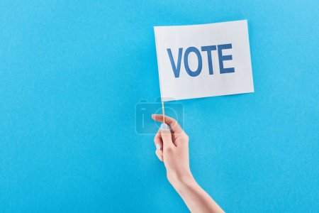 Photo for Partial view of woman holding white flag with vote lettering on blue background with copy space - Royalty Free Image