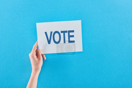 partial view of woman holding white card with vote lettering on blue background