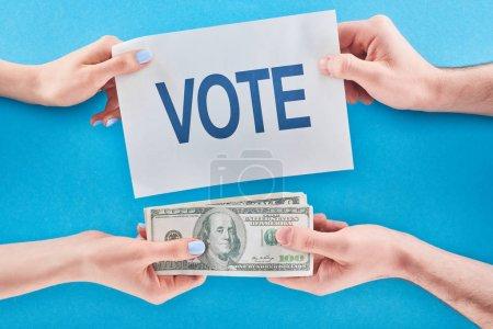 Photo pour Vue recadrée de l'homme donnant le pot-de-vin pour le vote à la femme sur le fond bleu - image libre de droit