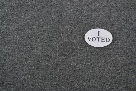 Photo pour Vue du haut de l'insigne avec j'ai voté lettrage sur fond texturé - image libre de droit