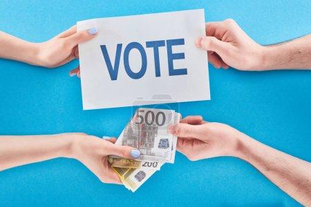 Photo pour Vue partielle de l'homme donnant le pot-de-vin pour le vote à la femme sur le fond bleu - image libre de droit